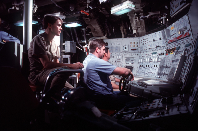 Three crewmen work in the control room as a fourth crewman looks on from behind during precommissioning activities aboard the nuclear-powered ballistic missile submarine OHIO (SSBN-726). The three men at work are, from left, ENS P. Price, IC2 (SS) Berge and MMC S. I. Brown