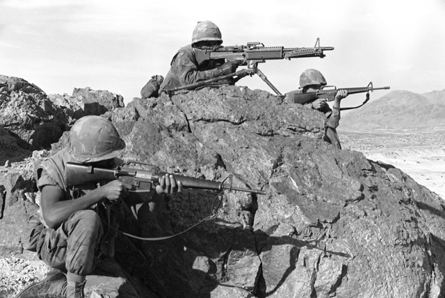 Three members of the Combat Engineers Battalion are in the offensive position on a mountain during Operation CAX-1-2-82. They are equipped with a M-60A1 machine gun and M-16A1 rifles