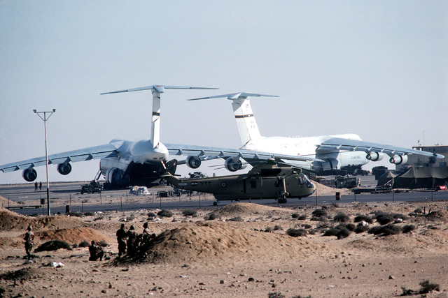Two Air Force C-5A Galaxy aircraft are offloaded during exercise Bright Star '82. AN Egyptian SH-3 Sea King helicopter is parked in the foreground