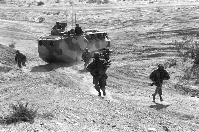 Two combat ready fire teams debark an LVTP-7 tracked landing vehicle and assault a hill during Operation CAX-1-2-82