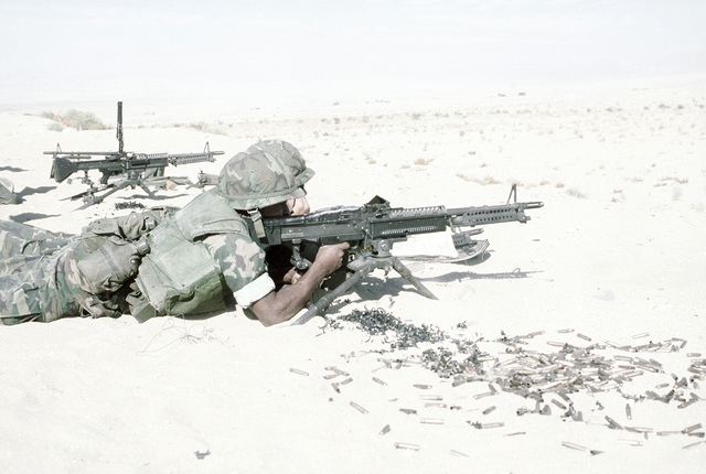 Two combat-ready Marines, an M-60A1 gunner and his assistant, are practice-firing the M-60A1 machine gun. The Marines are participating in Operation CAX 1-2-82 at the Marine Corps Air-to-Ground Combat Center