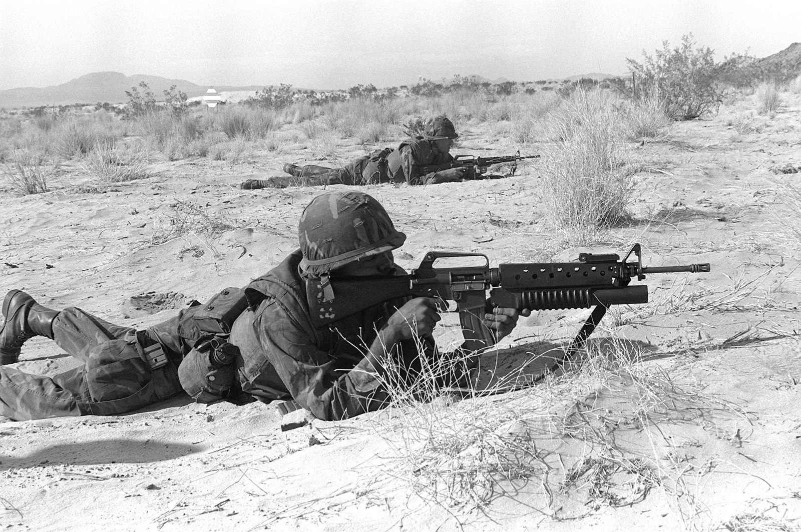 Two combat ready Marines are in the prone position with their M-16A1 rifles and an M-203 40mm grenade launcher attacked to the first rifle. The Marines are approaching their objective during Operation CAX-1-2-82