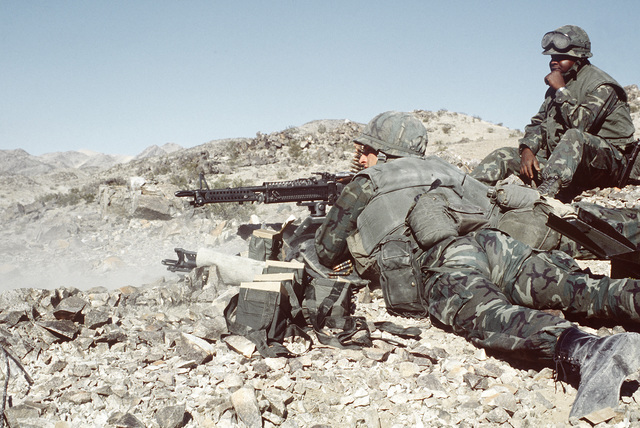 Two combat-ready Marines from Weapons Co., 1ST Bn., 8th Marines, armed with M-60A1 machine guns, man an observation post during Operation CAX 1-2-82 at the Marine Corps Air-to-Ground Combat Center
