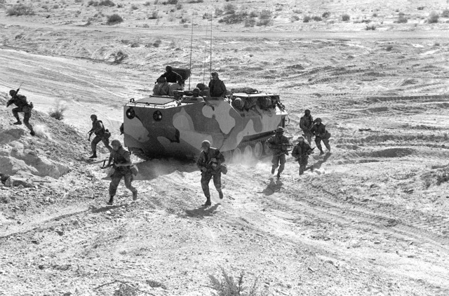 Two fire teams from Co. A,1ST Bn., 8th Marines, debark an LVTP-7 tracked landing vehicle and assault a hill during Operation CAX-1-2-82