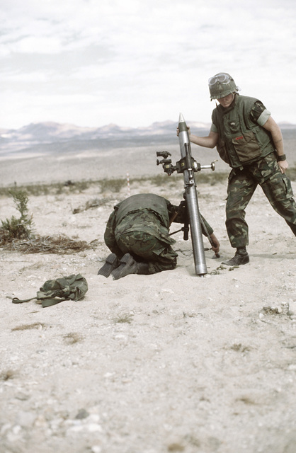 Two Marines from Weapons Company prepare to fire their M-29 81mm mortar. The Marines are participating in Operation CAX 1-2-82 at the Marine Corps Air-to-Ground Combat Center