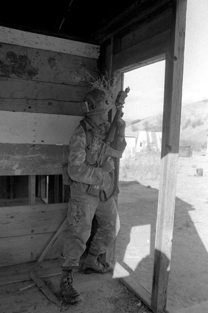 In combat town, PFC Don Williams of Company B, 1ST Battalion, 4th Marines, prepares to assault a building. His M-16A1 rifle is equipped with the Multiple Integrated Laser Engagement System (MILES)