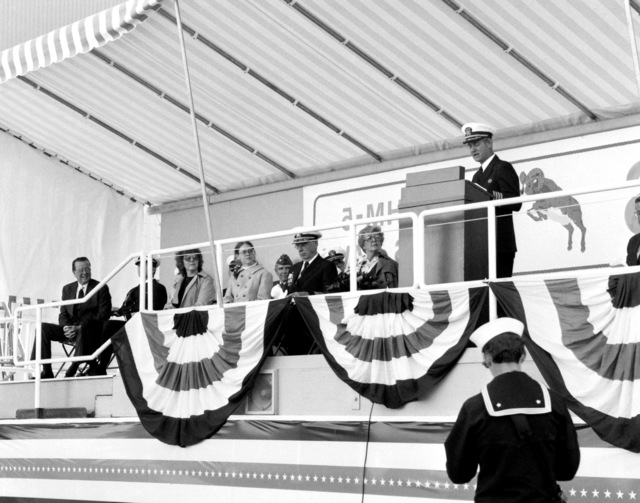 CAPT William E. Trueblood, PHM Acquisition Project Manager, Naval Sea Systems Command, speaks at the launching of the guided missile patrol combatant (hydrofoil) ARIES (PHM-5). Among those on the platform with Trueblood are, from left, Boeing Marine Systems Vice President Robert E. Bateman and VADM and Mrs. Earl B. Fowler Jr., VADM Fowler, commander, Naval Sea Systems Command, and Mrs. Fowler is the ship's sponsor