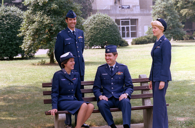 CPT Joe Marston, CPT Maria Sladek, seated, CAPT Vane Chalfont and CPT Carolyn Poatec model Class B uniforms in the Pentagon Courtyard