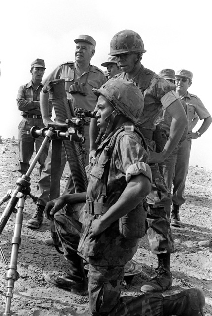 Three U.S. Marines of Weapons Co. 3rd Bn., 6th Mar., demonstrate the setting up of their 81mm mortar. Looking on are a general and other Peruvian military officers. They are all a part of the joint amphibious landing exercise Unitas XXII
