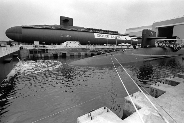 """A port bow view of the nuclear-powered ballistic missile submarine USS OHIO (SSBN-726) secured in the water during its commissioning. The partially-constructed nuclear-powered ballistic missile submarine GEORGIA (SSBN-729) is nearby displaying a """"Good Luck Ohio"""" banner"""