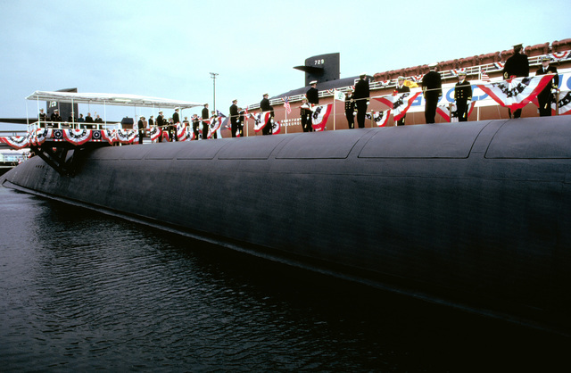 A starboard side view of the nuclear-powered ballistic missile submarine USS OHIO (SSBN-726) as crewmen man the rails and distinguished guests stand on the speaker's platform during the commissioning ceremony. The partially-constructed nuclear-powered ballistic missile submarine GEORGIA (SSBN-729) can be seen in the background. Both ships are products of General Dynamics Corp