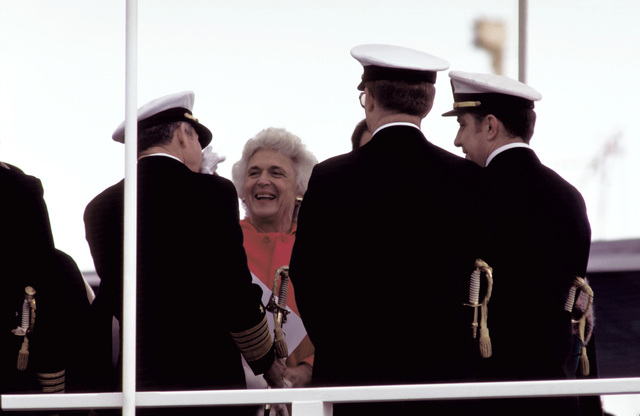 ADM Thomas B. Hayward, chief of naval operations, kisses the hand of Barbara Bush, wife of Vice President George H. W. Bush, while other officers look on during the commissioning of the nuclear-powered ballistic missile submarine USS OHIO (SSBN-726). The OHIO was built by General Dynamics Corp