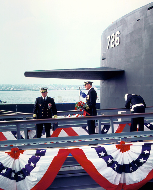 CAPT Alton K. Thompson, left, commanding officer (blue crew), and CAPT Arlington F. Campbell, commanding officer (gold crew), stand near the sail of the nuclear-powered ballistic missile submarine USS OHIO (SSBN-726) before presenting flowers to a distinguished guest during the commissioning ceremony. The union jack is waving in the background