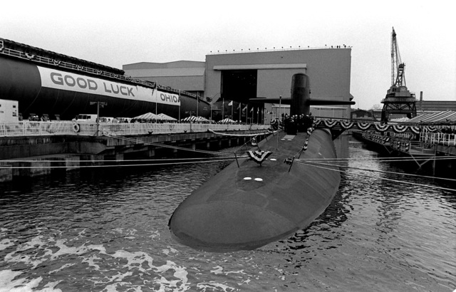 """Crewmen stand near the sail of the nuclear-powered ballistic missile submarine USS OHIO (SSBN-726) while it is secured during the commissioning ceremony. The """"Good Luck Ohio"""" sign to the left is being displayed on the hull of the nuclear-powered ballistic missile submarine GEORGIA (SSBN-729)"""