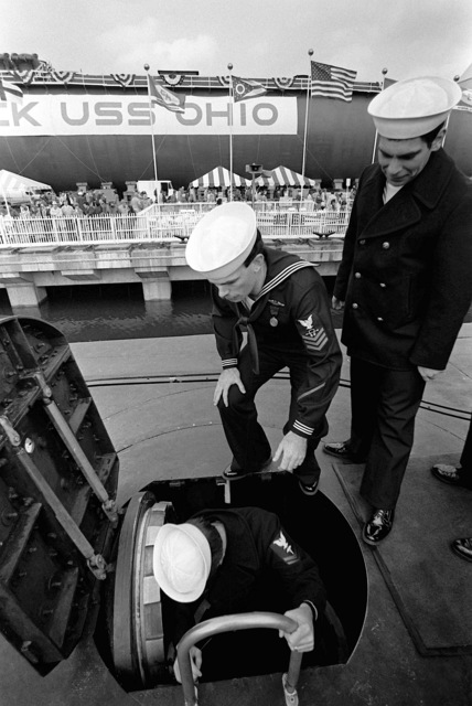 Crewmen use the hatch to go below following the commissioning ceremony aboard the nuclear-powered ballistic missile submarine USS OHIO (SSBN-726). The submarine was built by General Dynamics Corp