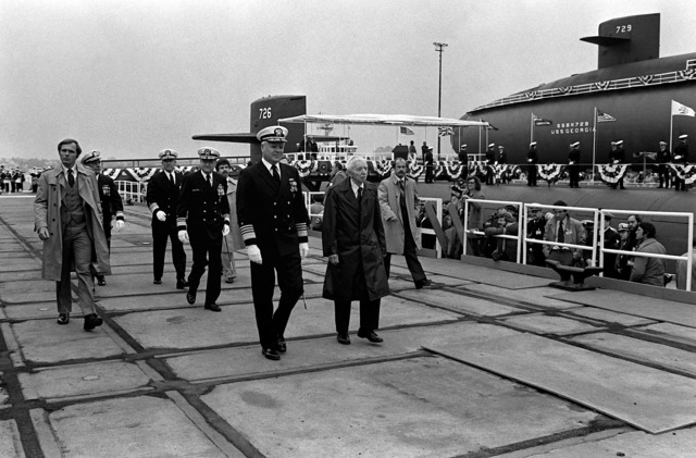 Flag officers walk along the pier prior to the commissioning of the nuclear-powered ballistic missile submarine USS OHIO (SSBN-726). They are, front to back: ADM Hyman G. Rickover, in civilian clothes; ADM Harry Train II, front; VADM Steven A. White, middle; and ADM Thomas B. Hayward. The submarine was built by General Dynamics Corp