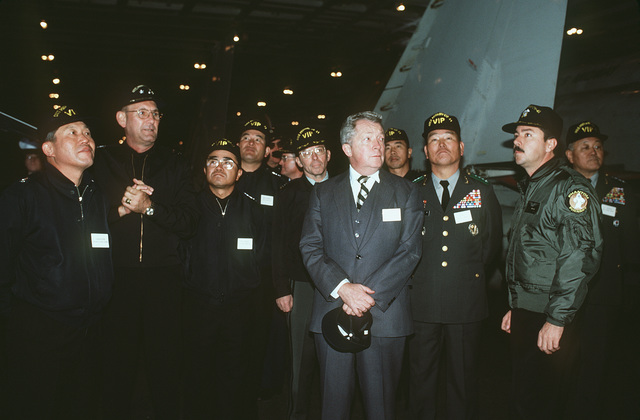 Richard Walker, center, US ambassador to South Korea, and other distinguished guests listen as a pilot explains carrier operations during a tour of the aircraft carrier USS MIDWAY (CV 41)