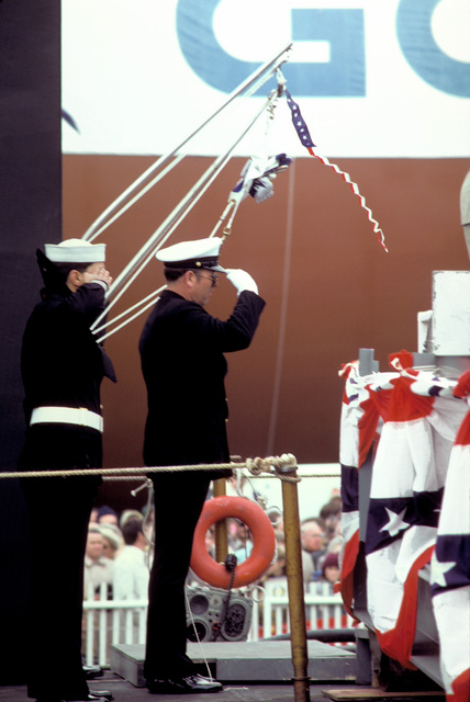 Two crewmen salute during the commissioning of the nuclear-powered ballistic missile submarine USS OHIO (SSBN-726). The OHIO was built by General Dynamics Corp