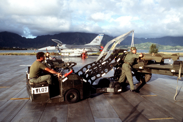 Airmen use a bomb loader to remove one of the Mark 82 500-pound laser-guided bombs from a munitions cart during exercise COPE ELITE '81. The F-16 Fighting Falcon aircraft (in the background) which will carry the bombs is from 428th Tactical Fighter Squadron, 474th Tactical Fighter Wing