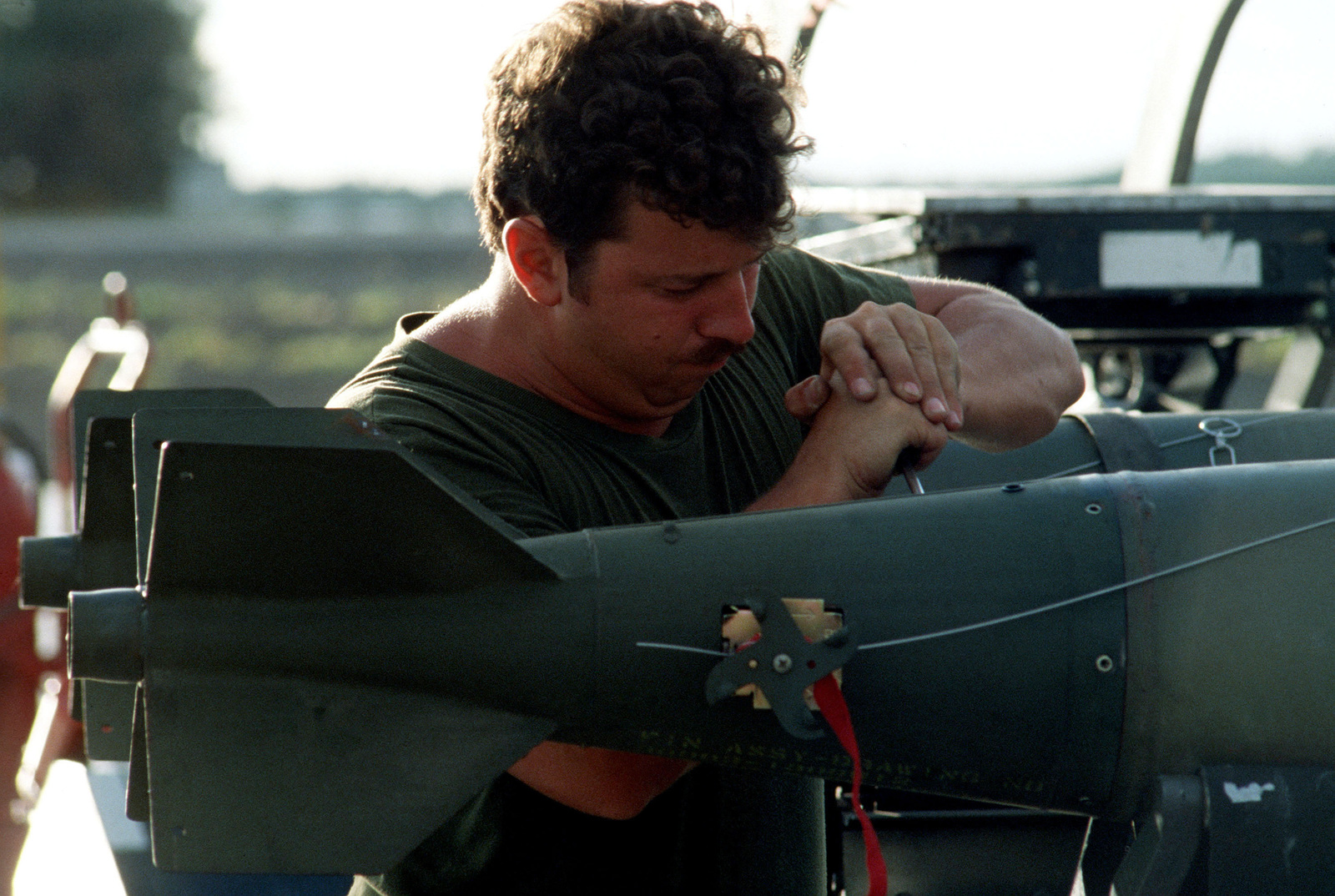STAFF Sergeant Bruce Boyer defuses Mark 82 500-pound laser-guided bombs for removal from a munitions cart during exercise COPE ELITE '81. The bombs will be loaded on an F-16 Fighting Falcon aircraft