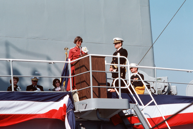 Barbara Griffiths, sponsor and wife of retired Vice Admiral (VADM) Charles H. Griffiths, speaks during the commissioning of the fleet oiler USS MERRIMACK (AO 179) at Avondale shipyard. Commander (CDR) Steven M. Mondul, commanding officer, is on the right