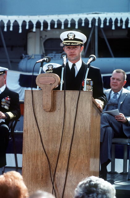 Commander Alan W. Swinger, prospective commanding officer, speaks during the commissioning ceremony for the Oliver Hazard Perry class guided missile frigate USS JOHN A. MOORE (FFG 19). Seated behind him (far left) is Rear Admiral Paul T. Gillerist, commander, Naval Base, San Diego, California, and Len Thorell, (far right) Vice President and General Manager of Todd Pacific Shipyards