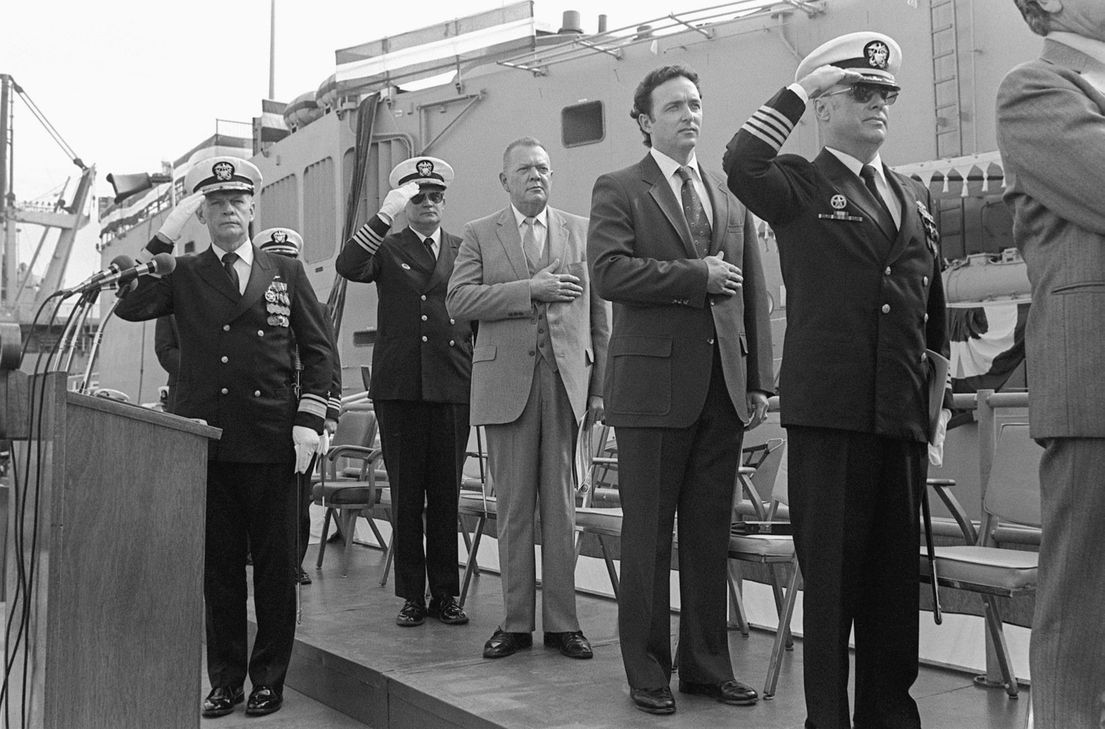 Guests on the speakers platform pay honor to the flag during the commissioning of the guided missile frigate USS JOHN A. MOORE (FFG 19). The guests are: Rear Admiral P. T. Gillcrist (at the podium), commander, Naval Base, San Diego; (left to right) Captain D. Kalb, Supervisor of Shipbuilding, Conversion and Repair; L. Thorell, vice president and general manager, Todd Pacific Shipyards; Congressman Dan Lungren (R-California), and Captain E. Russell, commander, Destroyer Squadron Nine