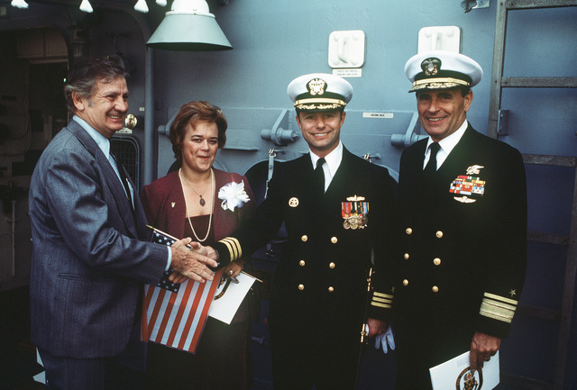 Mr. G. C. Jones shakes hands with Commander Alan W. Swinger, prospective commanding officer, as Ship's Sponsor Virginia Moore and a distinguished guest look on during the commissioning ceremony of the Oliver Hazard Perry class guided missile frigate USS JOHN A. MOORE (FFG 19). (SUBSTANDARD)