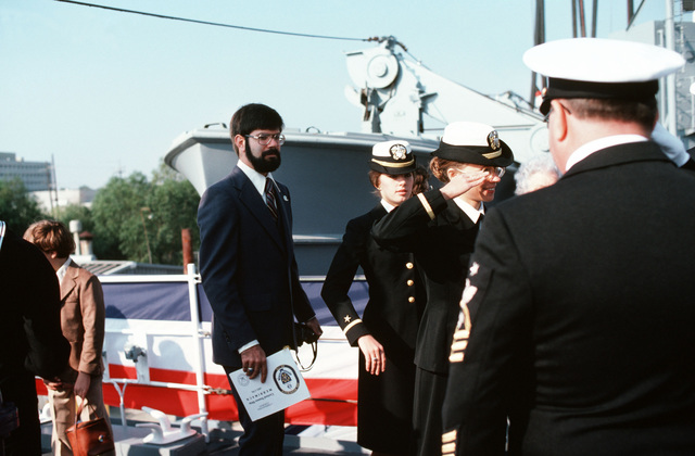 Naval officers and guests arrive at the commissioning of the fleet oiler USS MERRIMACK (AO 179) at the Avondale shipyard