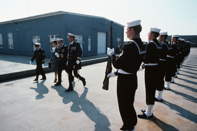Naval officers and guests pass an honor guard as they arrive at the commissioning of the fleet oiler USS MERRIMACK (AO 179) at Avondale shipyard