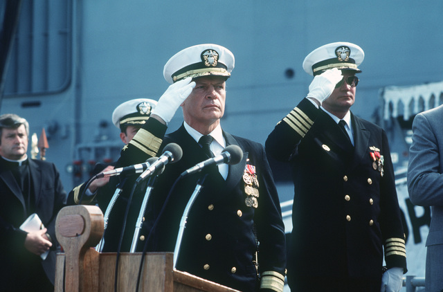 Rear Admiral Paul T. Gillerist, commander, Naval Base San Diego, and Captain David Kalb, Supervisor of Shipbuilding, Conversion and Repair, salute during the commissioning ceremony for the Oliver Hazard Perry class guided missile frigate USS JOHN A. MOORE (FFG 19)