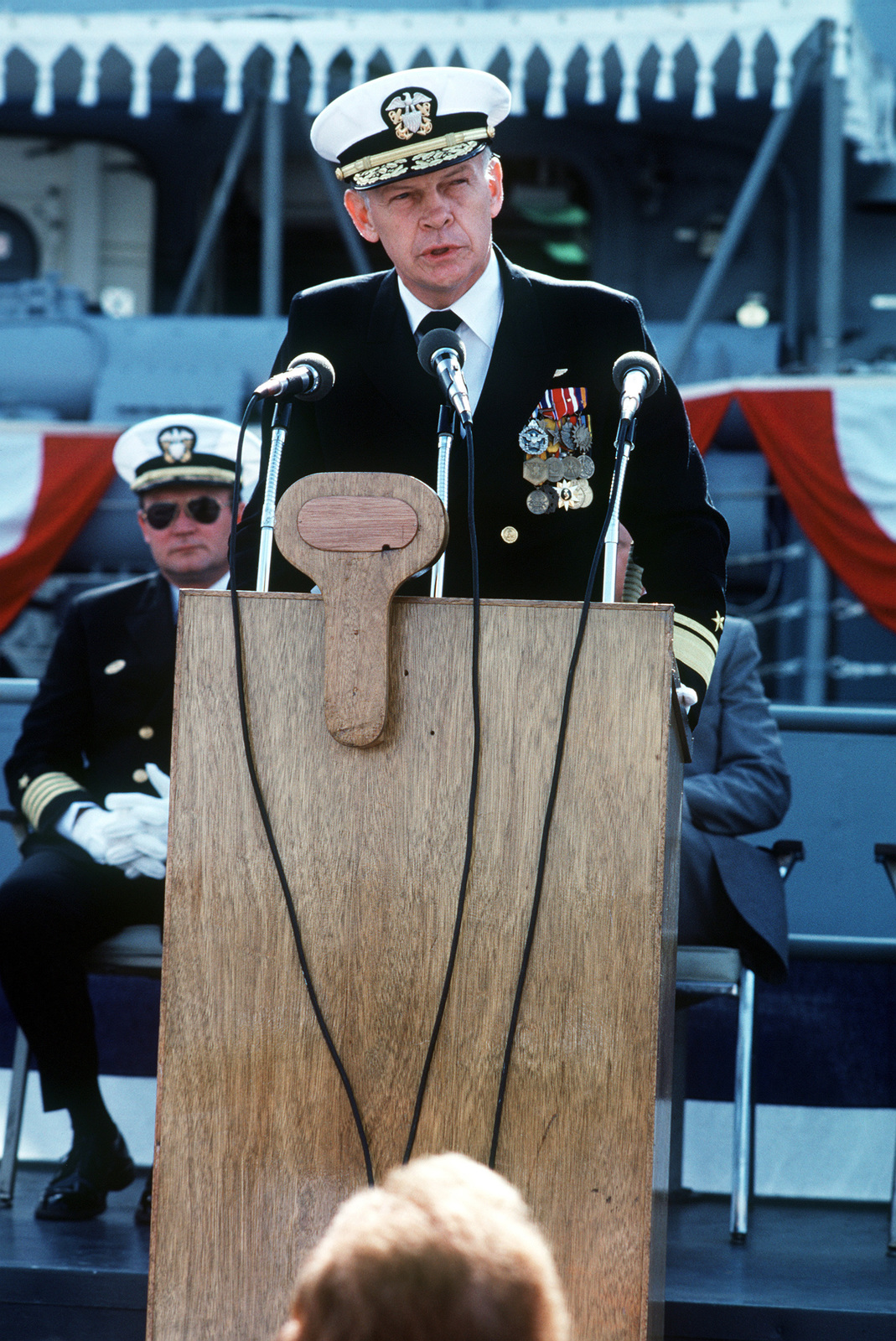 Rear Admiral Paul T. Gillerist, commander, Naval Base San Diego, speaks during the commissioning ceremony for the Oliver Hazard Perry class guided missile frigate USS JOHN A. MOORE (FFG 19). Seated behind him is Captain David Kalb, Supervisor of Shipbuilding, Conversion and Repair