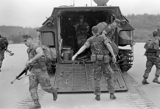 U.S. Marines of Co. K, 3rd Bn., 6th Marines, exit from an LVTP-7 tracked landing vehicle and hit the beach during Operation Unitas XXII. Militarymen from many South American countries are participating in the operation