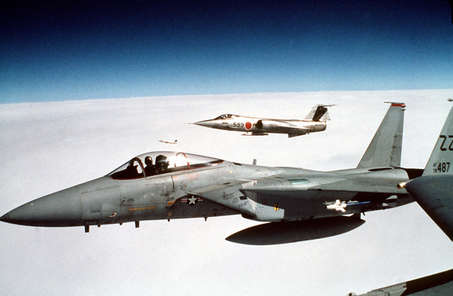 A left side view of an F-15 Eagle aircraft carrying an AIM-9 Sidewinder missile during exercise CAPE NORTH '80. Two F-104 Starfighter aircraft, from the 202nd Tactical Fighter Squadron, 5th Air Wing, Japanese Air Self Defense Forces, are in the background
