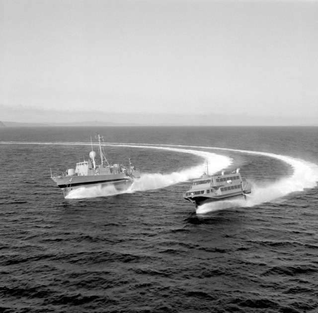 A port bow view of the guided missile combatant (hydrofoil) AQUILA (PHM-4), left, and the jetfoil BIMA SAMUDERA I making a right turn together during testing off the coast of Seattle. The two ships are being built by Boeing Marine Systems. The AQUILA will be delivered to me U.S. Navy in December 1981, and the BIMA SAMUDERA I will joint the Republic of Inodonesia navy in early 1982