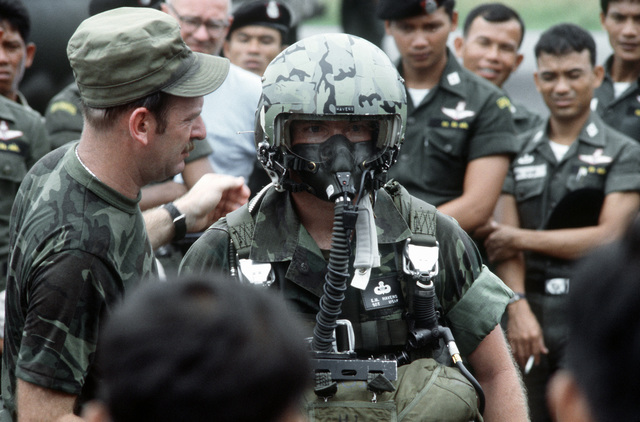A combat control team (CCT) member demonstrates the use of parachute gear to Thai paratroopers. The CCT is from the 374th Tactical Airlift Wing, involved in a joint parachute training exercise with Thai forces