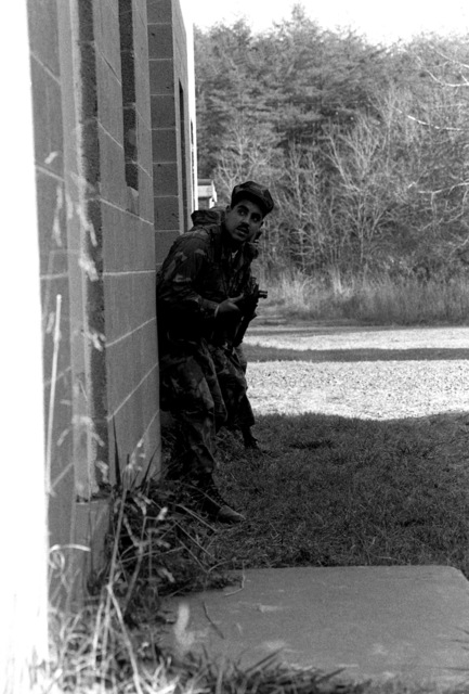 A military policeman looks around the corner of a building during a training exercise of the Pop-up Target Recognition Course