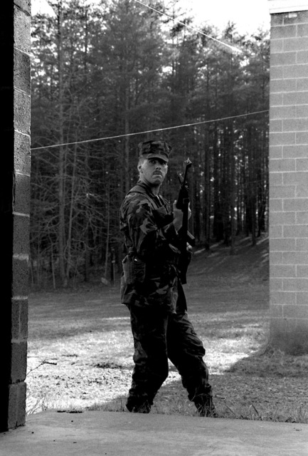 A military policeman looks cautiously into a building during a training exercise of the Pop-up Target Recognition Course