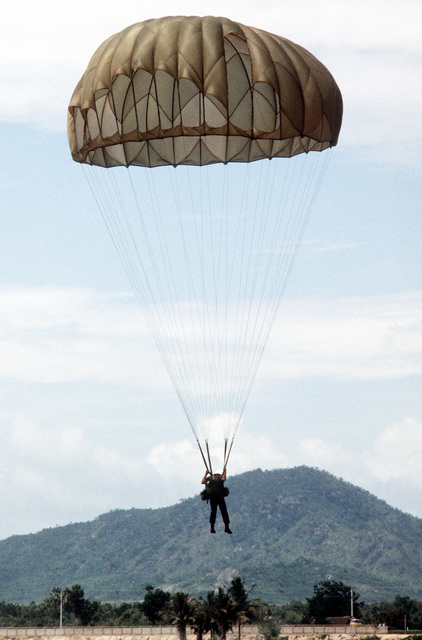 A paratrooper is approaching the ground after jumping from a C-130 Hercules aircraft. Members of Thai forces are involved in a joint parachute training exercise with a United States Air Force combat control team