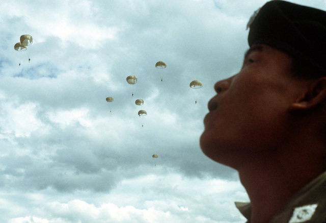 A Thai paratrooper, on the ground, watches his comrades parachuting after jump from a C-130 Hercules aircraft. Members of Thai forces are involved in a joint parachute training exercise with a United States Air Force combat control team