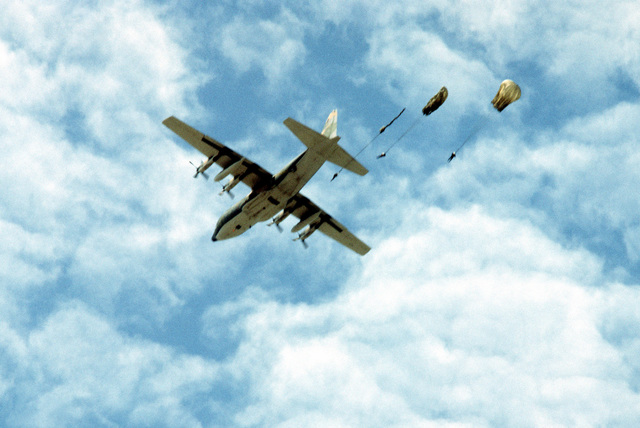 Bottom view of a C-130 Hercules aircraft as paratroopers jump from the aircraft. The aircraft is from the 21st Tactical Airlift Squadron. A United States Air Force combat control team is participating in a joint parachute training exercise with Thai forces