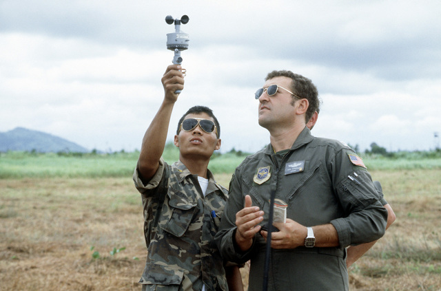 Combat control team (CCT) members and a Thai soldier use equipment to check weather as part of airdrop control procedure in a drop zone. The CCT is from the 374th Tactical Airlift Wing, involved in a joint parachute training exercise with Thai forces