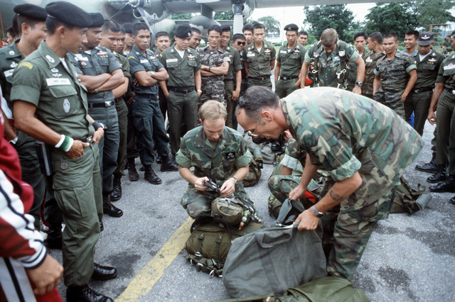 Combat control team (CCT) members demonstrate the use of parachute gear to Thai paratroopers. The CCT is from the 374th Tactical Airlift Wing, involved in a joint parachute training exercise with Thai forces