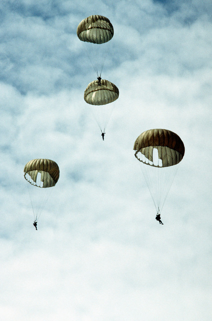 Paratroopers are approaching the ground after jump from a C-130 Hercules aircraft. Members of Thai forces are involved in a joint parachute training exercise with a United States Air Force combat control team