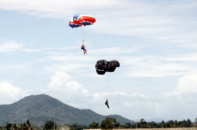Paratroopers are approaching the ground after jumping from a C-130 Hercules aircraft. Members of Thai forces are involved in a joint parachute training exercise with a United States Air Force combat control team