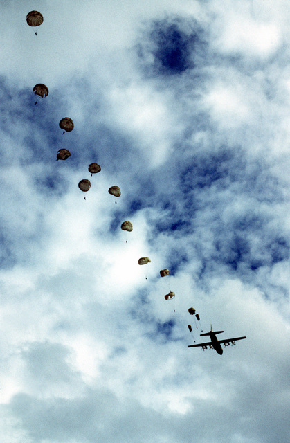 Paratroopers jump from a C-130 Hercules aircraft. Members of the Thai forces are involved in a joint parachute training exercise with a U.S. Air Force combat control team. The aircraft is from the 21st Tactical Airlift Squadron