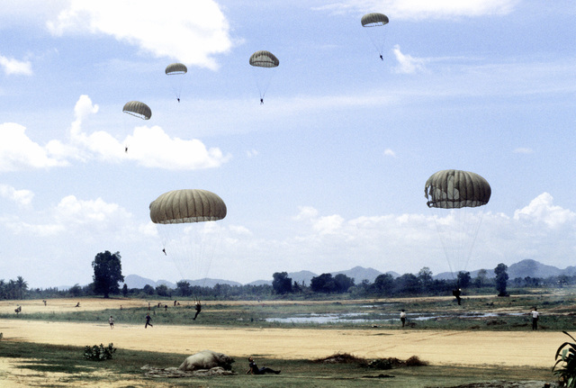 Soldiers are parachuting to the ground after jump from a C-130 Hercules aircraft. Members of Thai forces are involved in a joint parachute training exercise with a United States Air Force combat control team