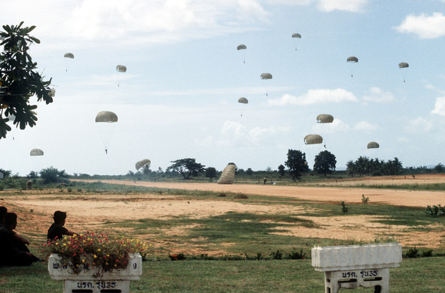 Thai paratroopers (left), watch their comrades parachuting to the ground after jumping from a C-130 Hercules aircraft. Members of Thai forces are involved in a joint parachute training exercise with a United States Air Force combat control team