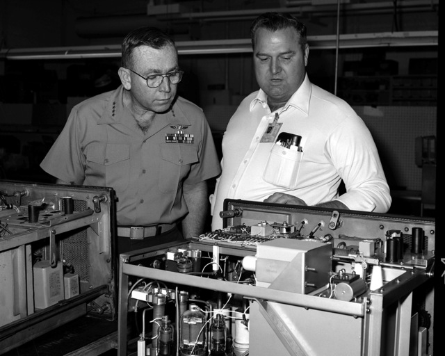 GEN P. X. Kelly, assistant commandant of the Marine Corps, is briefed on the detailed work involved in rebuilding a Unit 7 drawer AN/TPQ-10 by V.H. Carson Jr., a shop supervisor in Repair Division. Kelly was visiting the Marine Corps Logistics Base