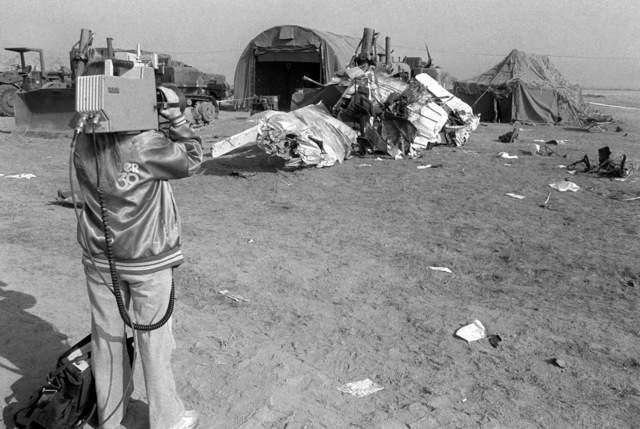 A television cameraman videotapes the wreckage of a civilian aircraft